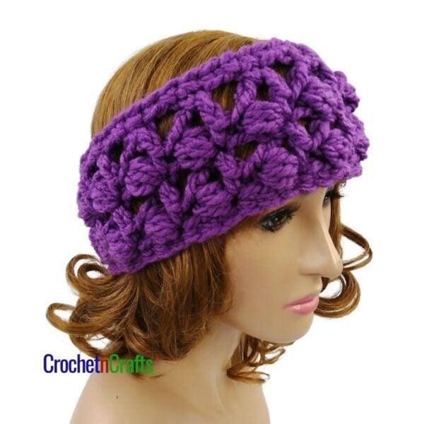 Slanted puffs crochet ear warmer worn on a small adult head.